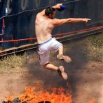 man jumping over fire pit