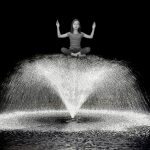 girl sitting on top of a water fountain