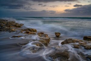 waves crashing against rocks on a beach