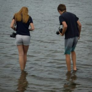 female and male in the water with cameras