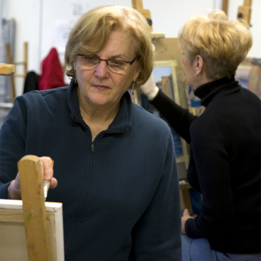 Two women painting on easels in an art class