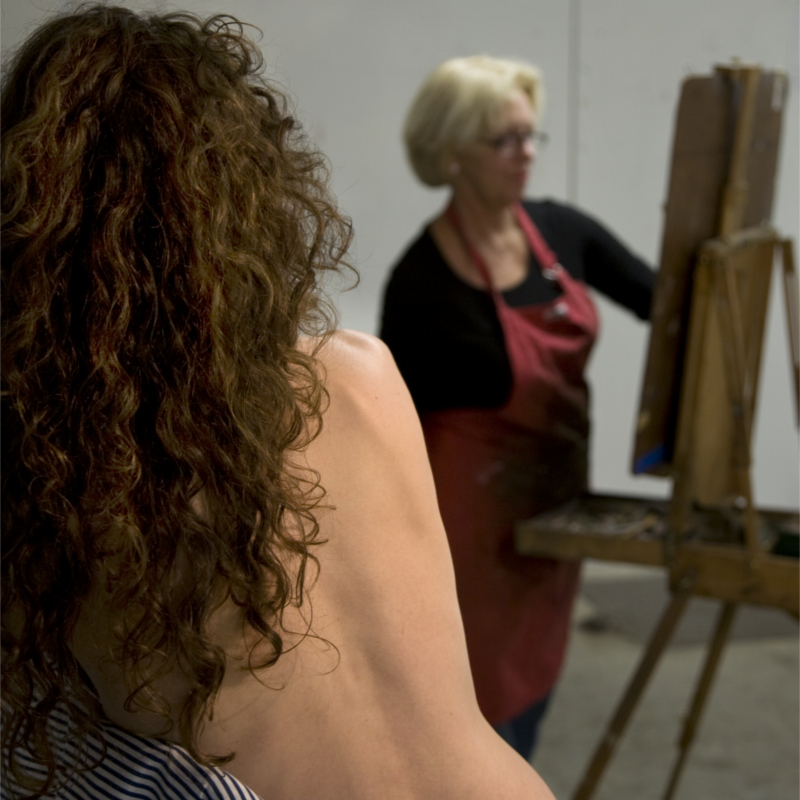 Woman in background with easel drawing, model in foreground with back to camera